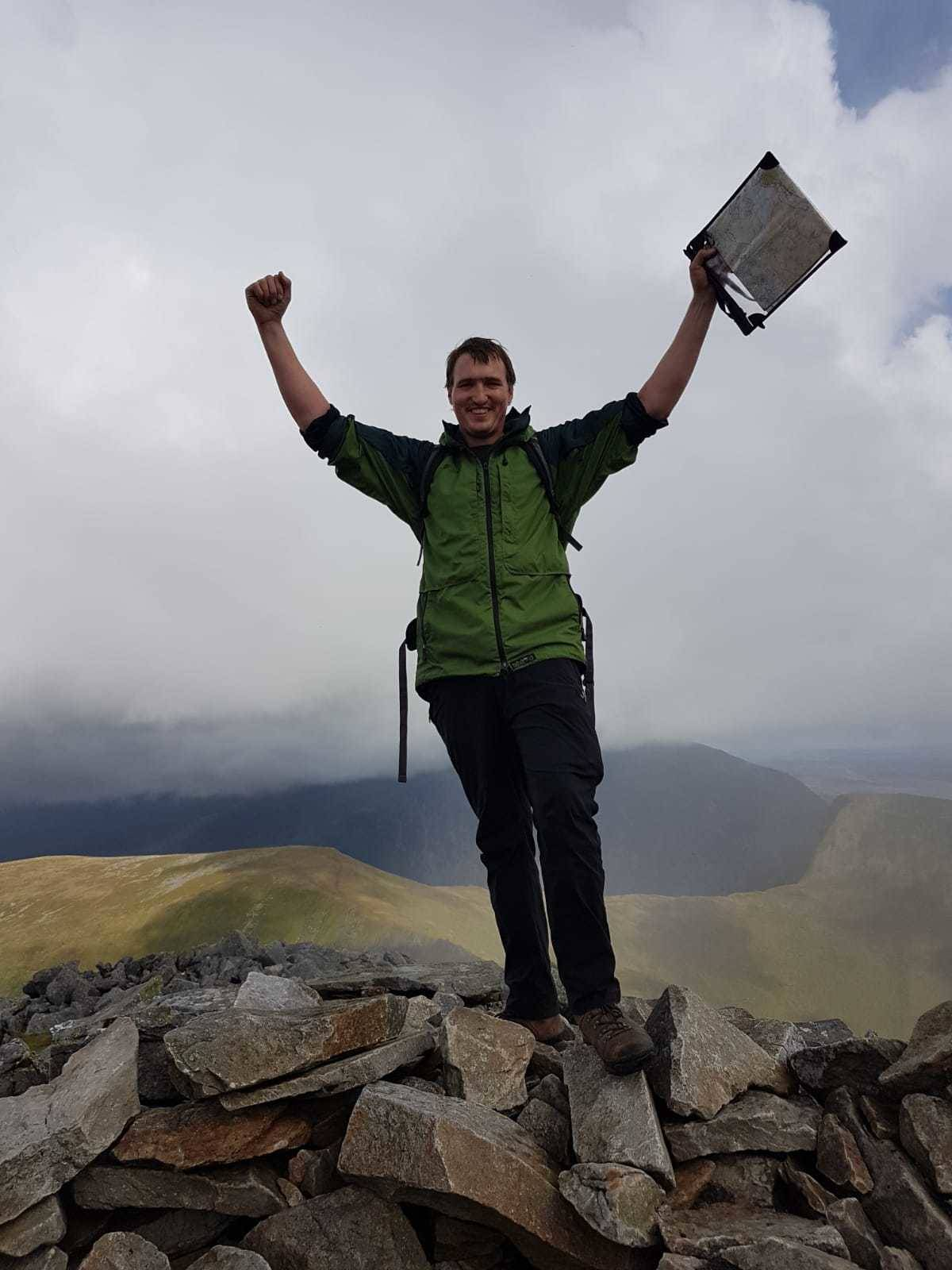 A photograph of a man standing at the top of a mountain with a map in his hand