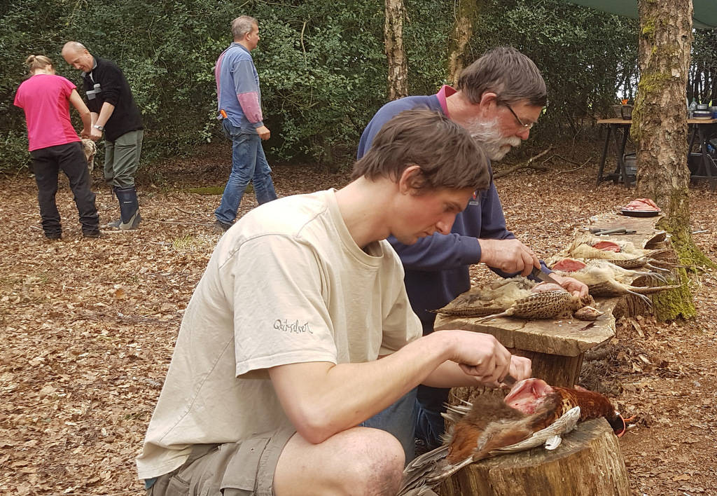 Two men preparing game in the woods at their Bushcraft experience