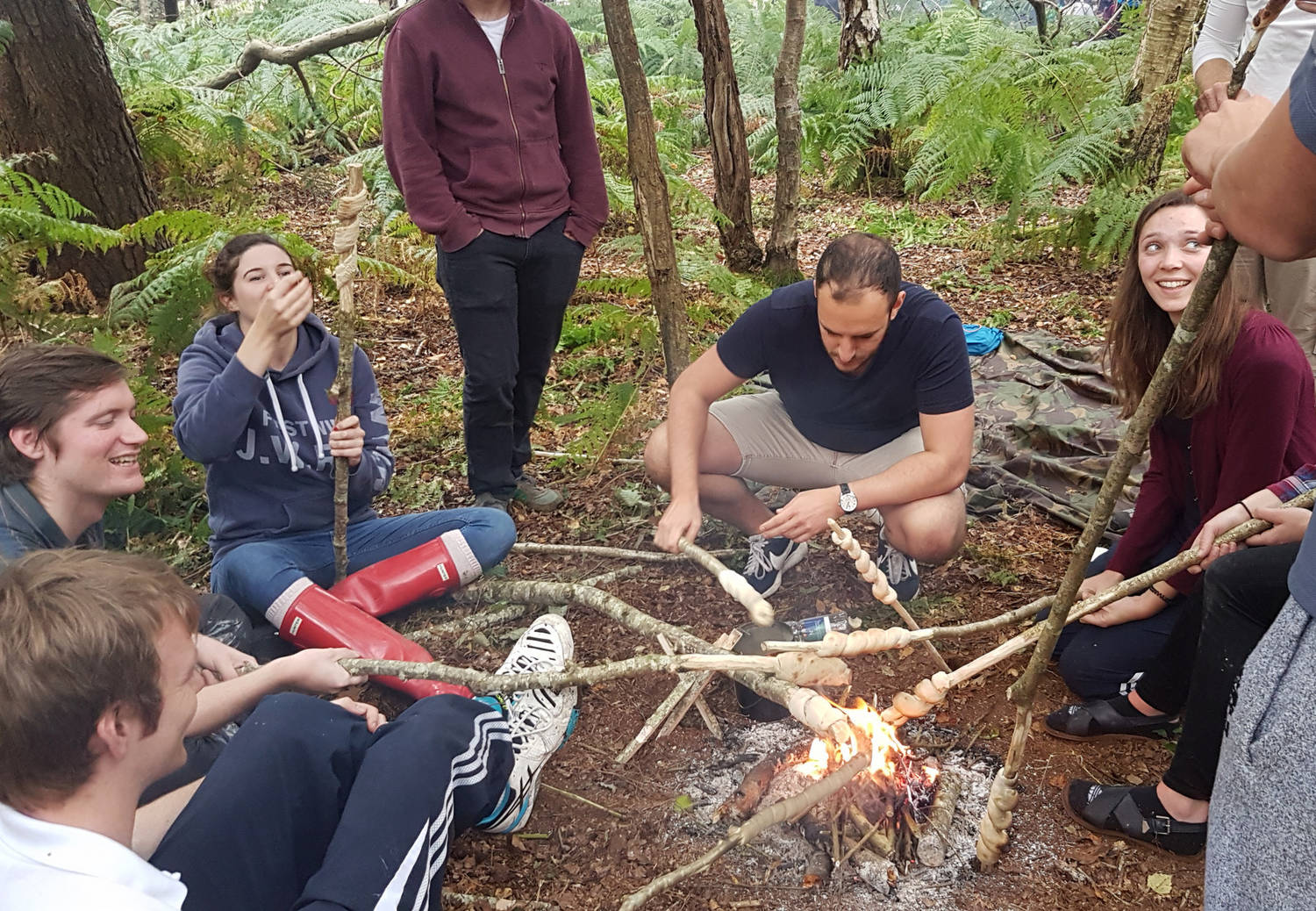 A group of people cooking over a campfire in the woods