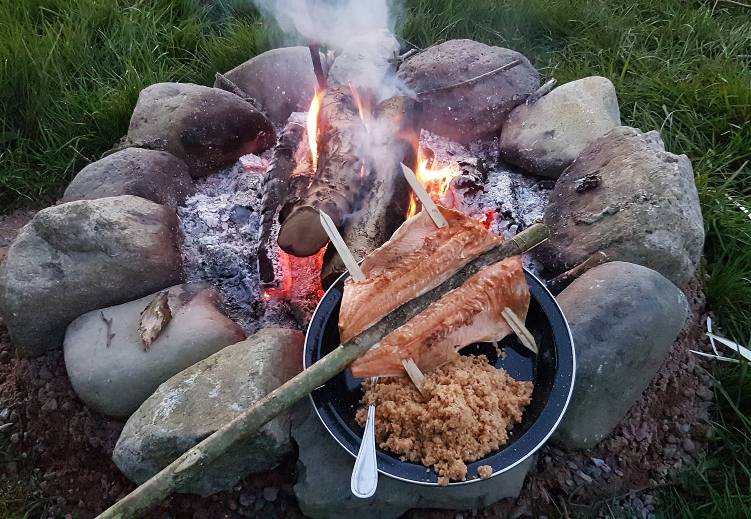 A photograph of cooked trout next to a campfire