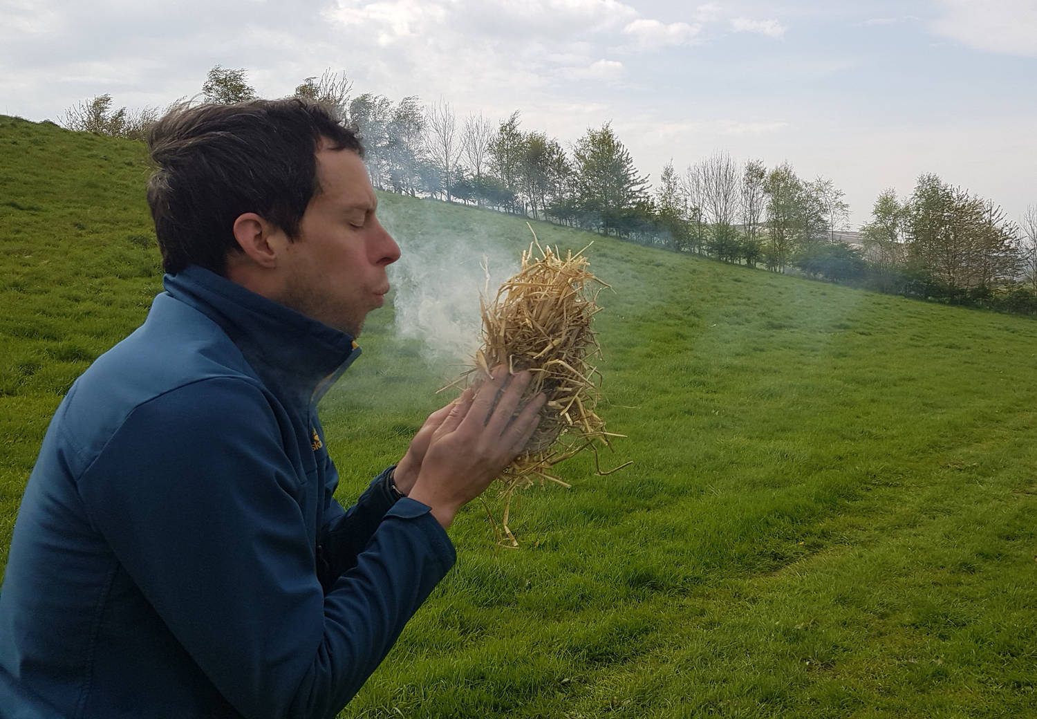 A photograph of a man blowing ona tinder bundle in a field.