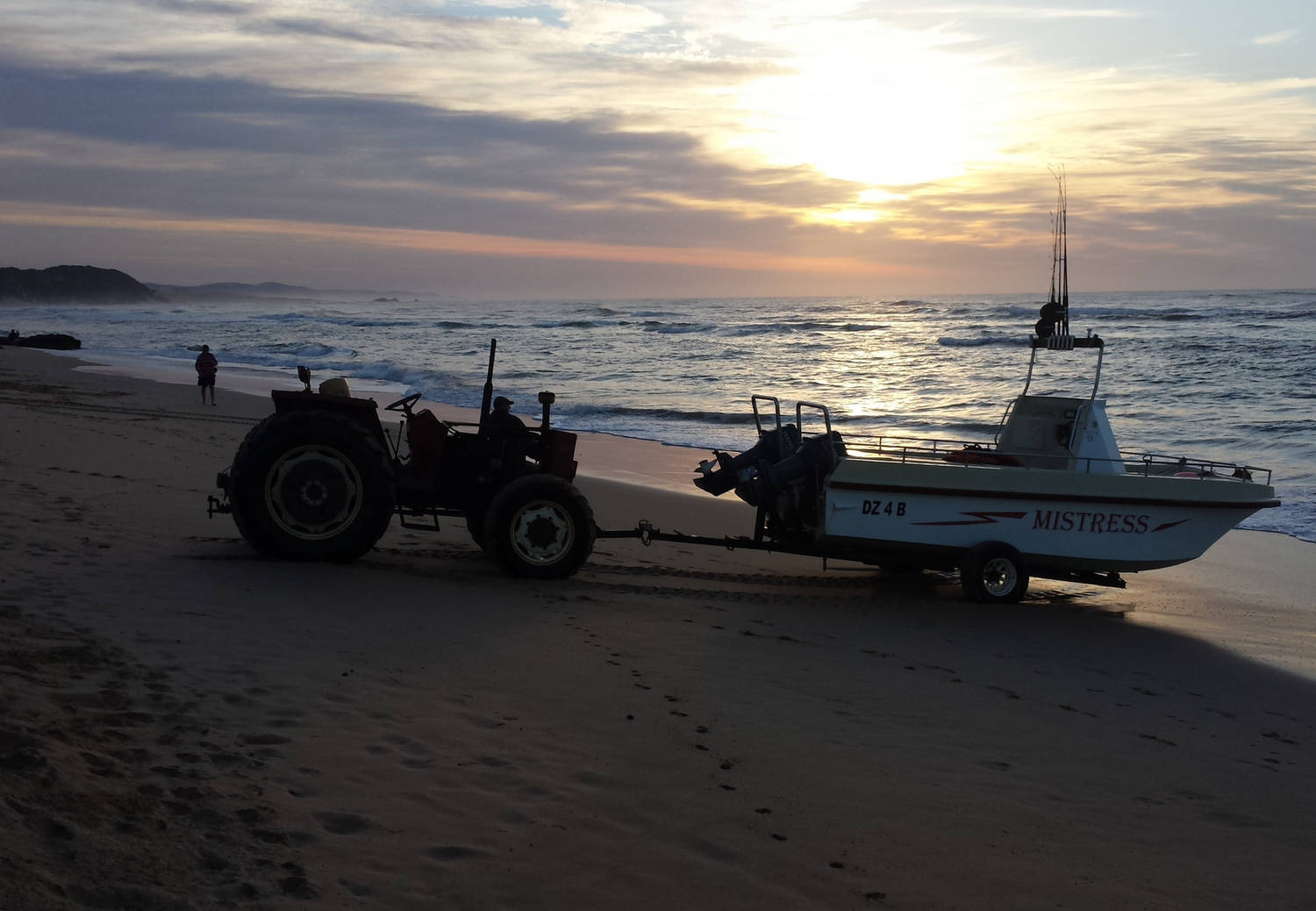 A photograph of a boat being towed on a beach near the sea shore at sunrise
