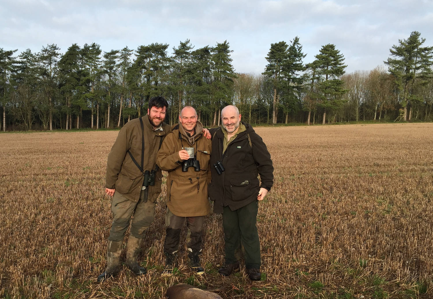 A photograph of three men in a field with hunting equipment