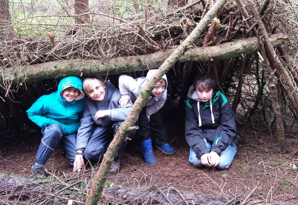 A photograph of 4 children under a shelter in the woods