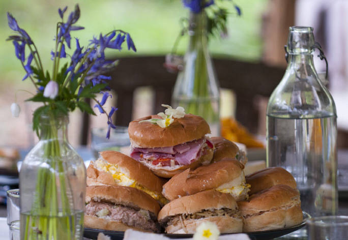 A photograph of sandwiches on a plate surrounded by flowers.