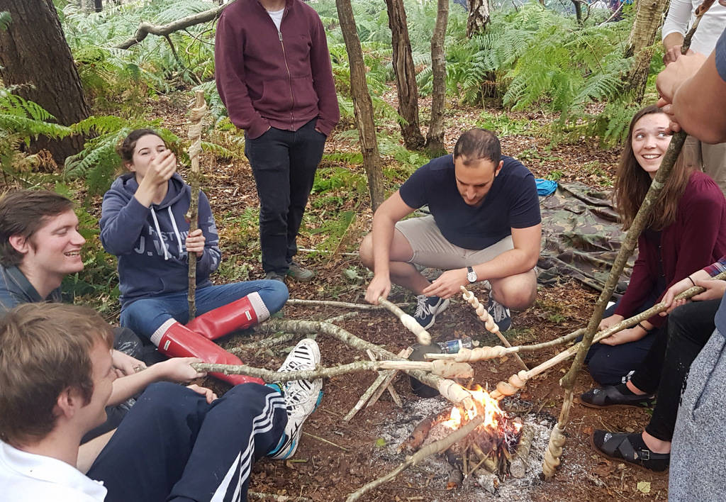 A group around a campfire making bread