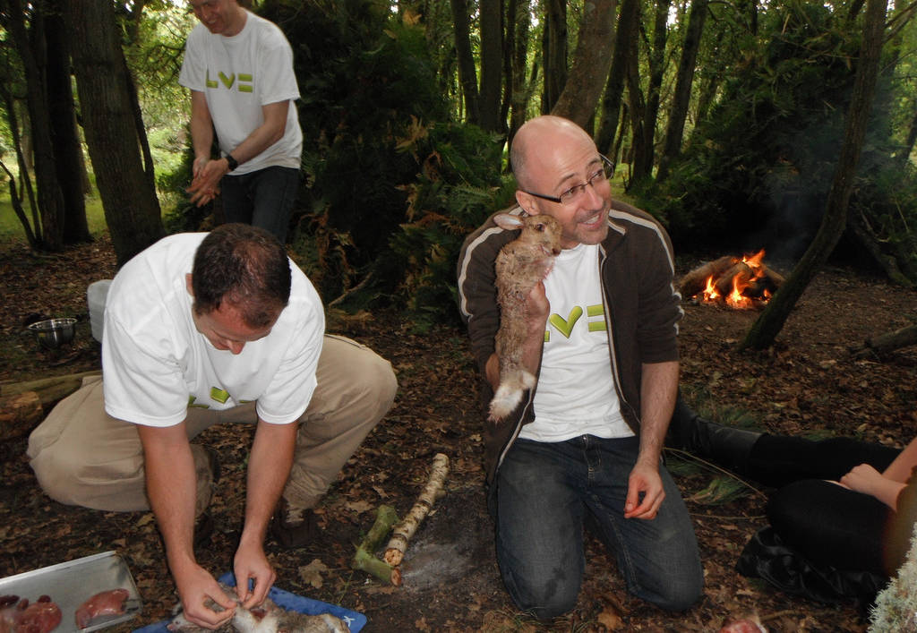 A corporate group preparing rabbit in the woods